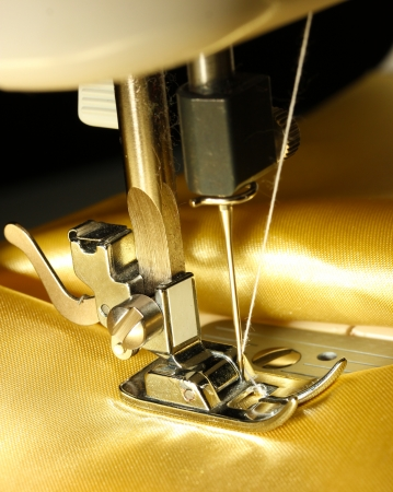 Sewing machine with gold cloth closeup photo