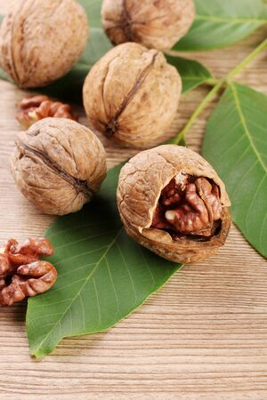 walnuts with green leaves, on wooden background Stock Photo - 15425472