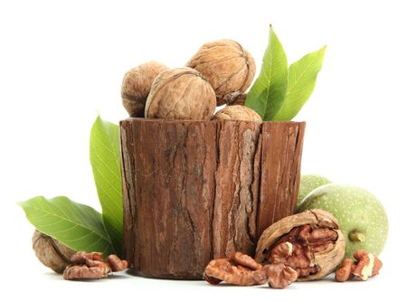 walnuts with green leaves in woooden vase, isolated on white Stock Photo - 15425482