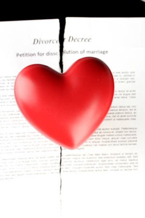 decree: red heart with torn Divorce decree document, on black background close-up