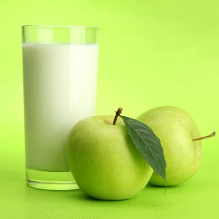 Glass of kefir and apples, on green background Stock Photo - 15426005