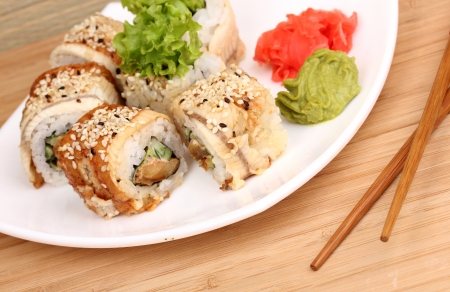 Tasty rolls served on white plate with chopsticks on wooden table close-up Stock Photo - 15458097