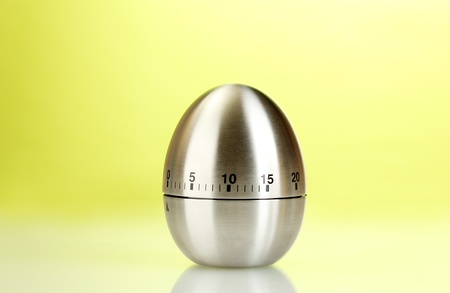 timescale: metal kitchen egg timer on a green background Stock Photo