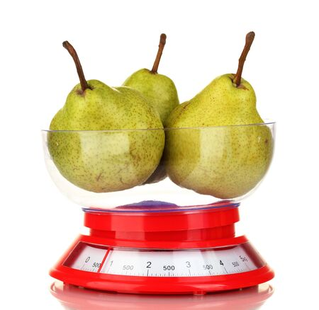 Ripe pears in kitchen scales isolated on white photo