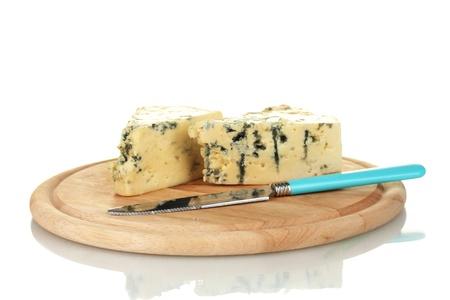 チーズのカビと白で隔離されるまな板の上のナイフ