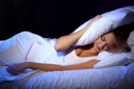 insomnio: hermosa mujer joven acostada en la cama en el dormitorio
