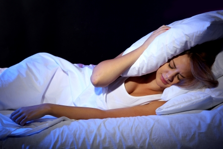 insomnia: young beautiful woman lying on bed in bedroom