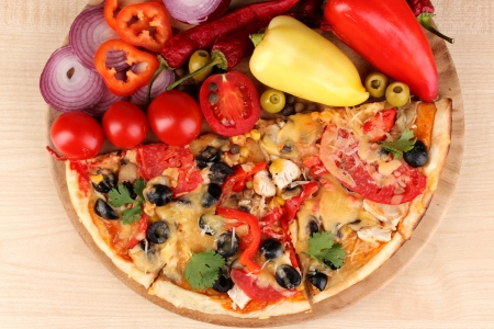 Delicious pizza with ingredients close-up on wooden table background photo