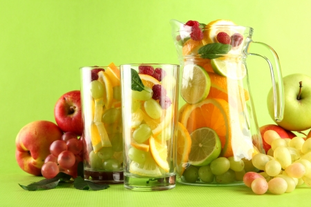 jar and glasses with citrus fruits and raspberries, on green background Stock Photo - 15457827