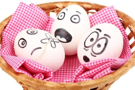 caras chistosas: Huevos blancos con caras divertidas en la cesta aislada en blanco