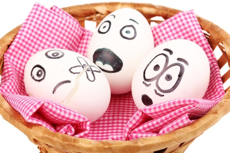 easter sign: White eggs with funny faces in basket isolated on white Stock Photo