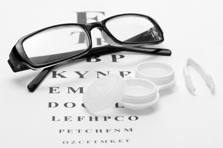 glasses, contact lenses in containers and tweezers, on snellen eye chart background photo
