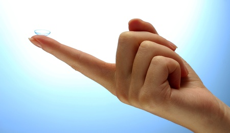 contact lens on finger on blue background Stock Photo - 15458613