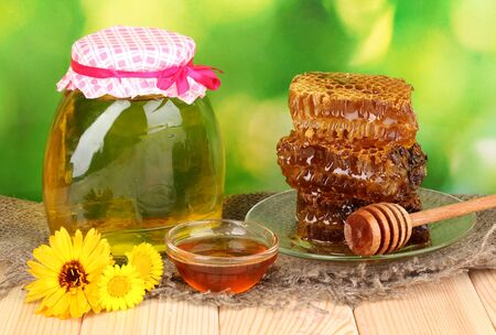 Jar of honey and honeycomb on wooden table on nature background photo
