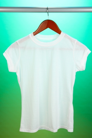 White t-shirt on hanger on green background photo