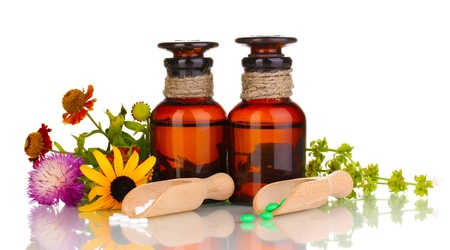 healing plant: medicine bottles with tablets and flowers isolated on white Stock Photo