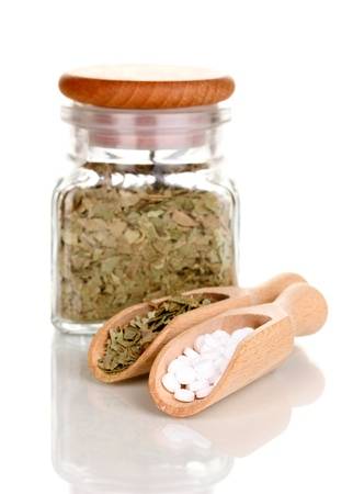 curative: tablets and bottle with herbs isolated on white