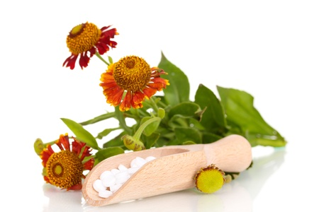 curative: homeopathic tablets and flowers isolated on white