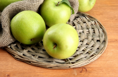 Ripe green apples with leaves on burlap, on wooden table photo