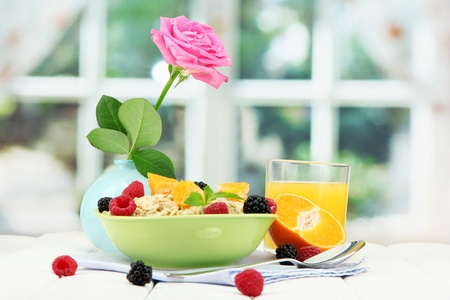 tasty oatmeal with berries and glass of juice on table, on window background Stock Photo - 15556779