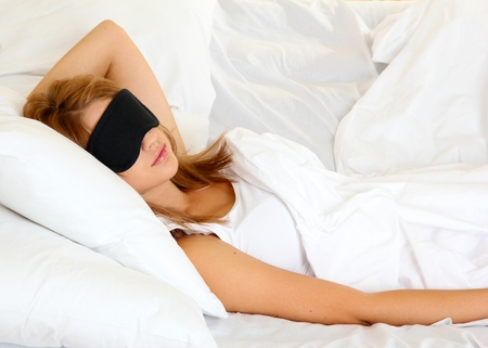 young beautiful woman sleeping in bed with eye mask photo