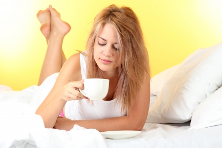 young beautiful woman on bed with cup of coffee on yellow background Stock Photo - 17129688