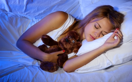 young beautiful woman with toy bear sleeping on bed in bedroom Stock Photo - 17129698