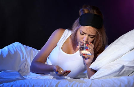 young beautiful woman with pills lying on bed in bedroom photo