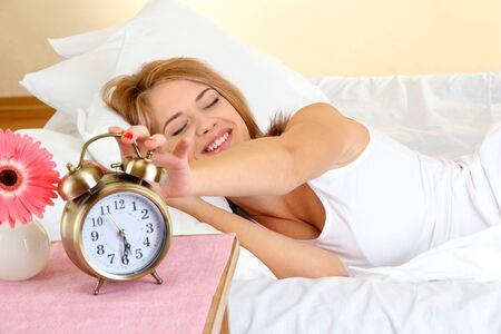 young beautiful woman sleeping on bed with alarm clock in bedroom photo
