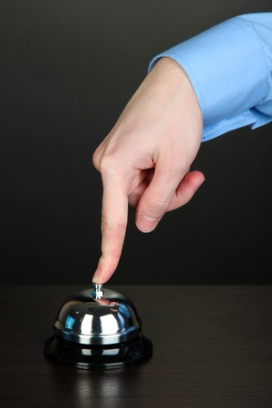 Hand ringing in service bell on wooden table on black background Stock Photo - 15563289