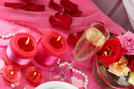 Table setting in honor of Valentine's Day on white fabric background photo