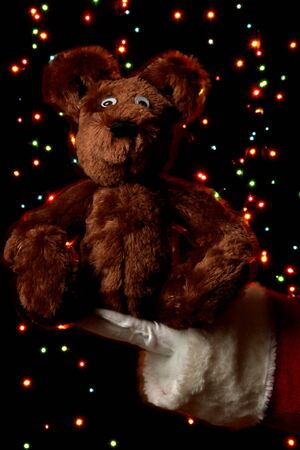 Santa Claus hand holding toy bear on bright background Stock Photo - 15556741