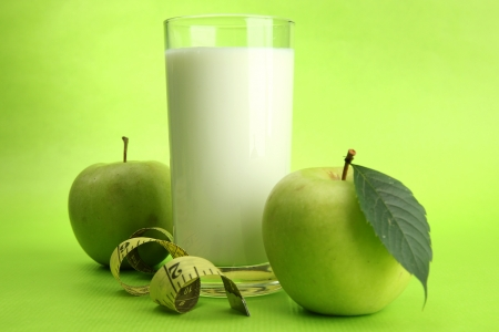 Glass of kefir, apples and measuring tape, on green background Stock Photo - 15540808