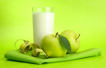 Glass of kefir, apples and measuring tape, on green background Stock Photo - 15545694