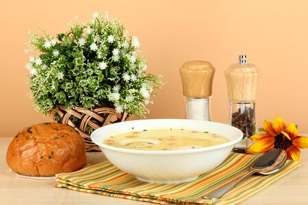Fragrant soup in white plate on table on beige background close-up photo