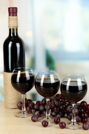 Red wine in glass on room background photo