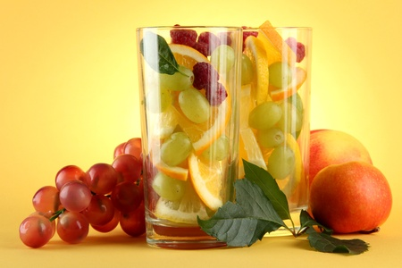 transparent glasses with citrus fruits, on yellow background Stock Photo - 15545756