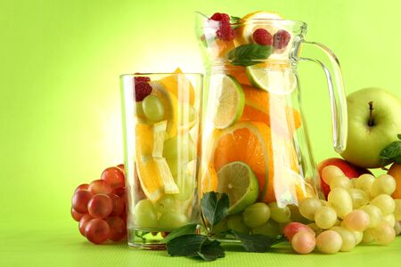 jar and glass with citrus fruits and raspberries, on green background Stock Photo - 15545785