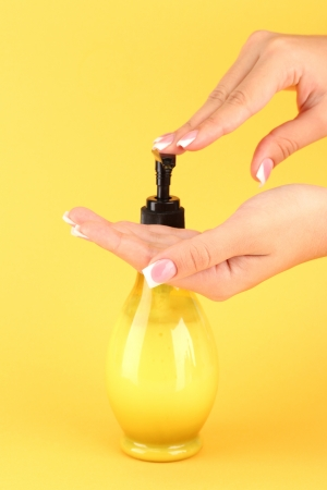 antibacterial soap: woman squeezing lotion on her hand, on yellow background close-up