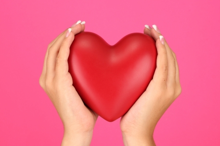 Red heart in woman's hands, on pink background close-up Stock Photo - 15545746