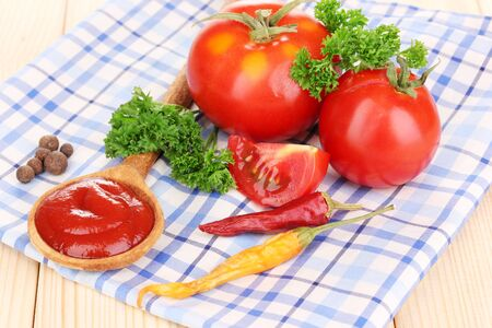Ketchup and ripe tomatoes on wooden table photo