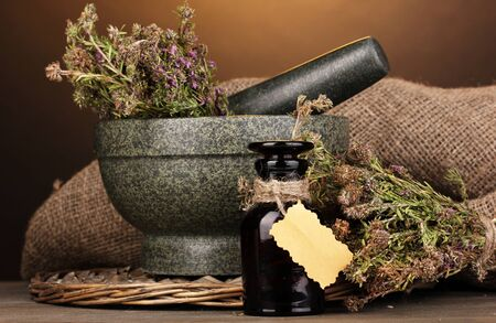 desiccated: Thyme herb and mortar on wooden table on brown background