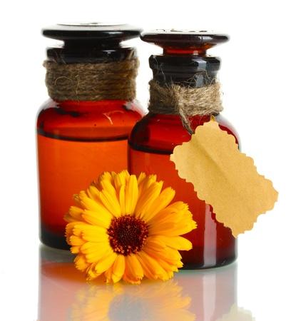curative: medicine bottles and beautiful calendula flower, isolated on white Stock Photo