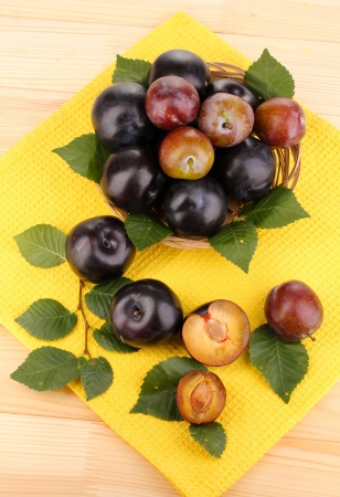 Rip plums on basket on wooden table photo