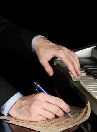 man hands playing piano and writes on parer for notes Stock Photo - 15582408