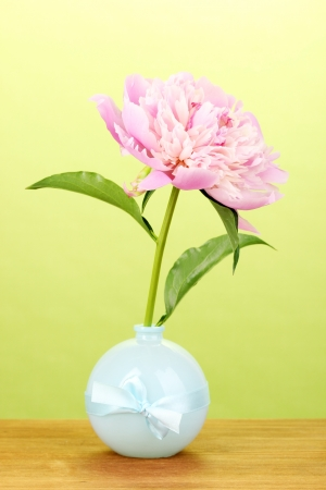 Pink peony in vase on wooden table on green background Stock Photo - 15643549