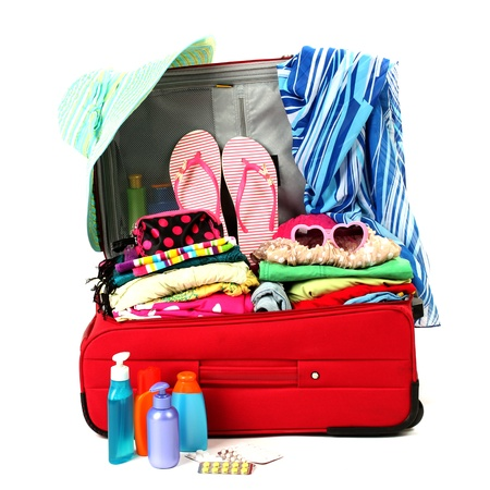 luggage pieces: Red travel suitcase with personal belongings isolated on white