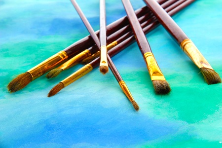 brushes on bright abstract gouache painted background photo