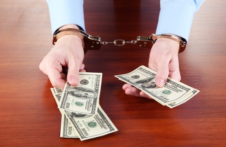 Businessman in handcuffs counts the money for bribes Stock Photo - 15661837