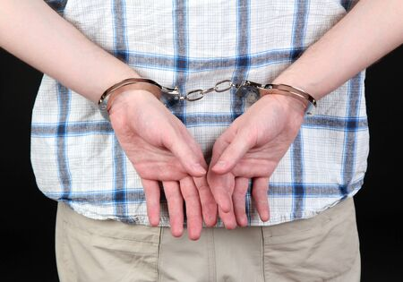 man in handcuffs on black background close-up photo